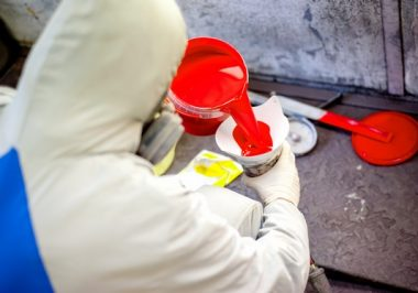 Auto mechanic mixing and pouring red paint for spraying and painting cars in industrial factory